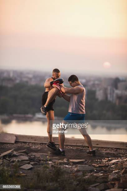 Two athletic men practicing kick boxing at sunset.