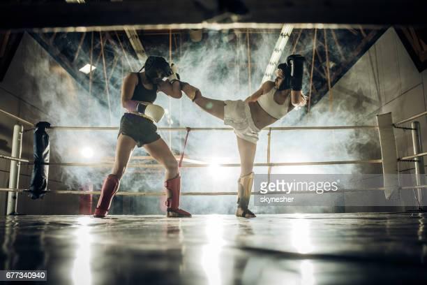 Två atletiska kvinnor kämpar på kickboxning matcher i ett gym.