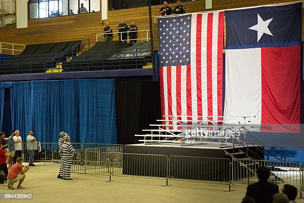 Two attendees dressed as Hillary and Bill Clinton in prison uniforms obey the pledge of allegiance before a Donald Trump rally at Travis County...