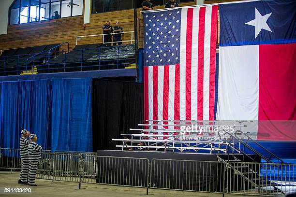 Two attendees dressed at Hillary and Bill Clinton in prison uniforms obey the pledge of allegiance before a Donald Trump rally at Travis County...