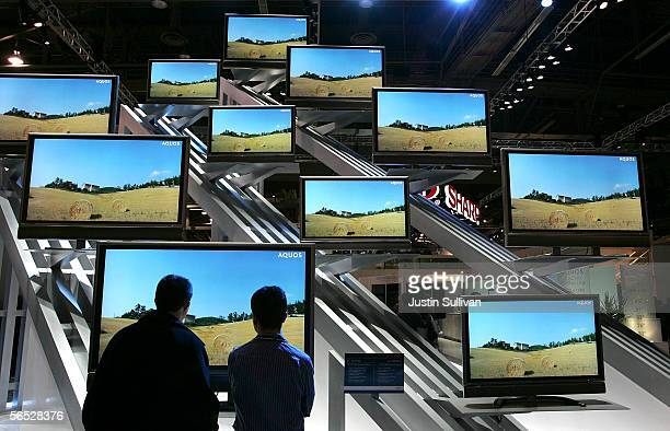 Two attendees look at a display of Aquos flat screen televisions on the opening day of the 2006 Consumer Electronics Show January 5, 2006 in Las...