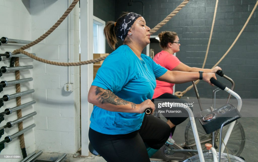 Two attractive body-positive women, Latino and Caucasian, doing a workout on the exercise bike in the gym : Stock Photo