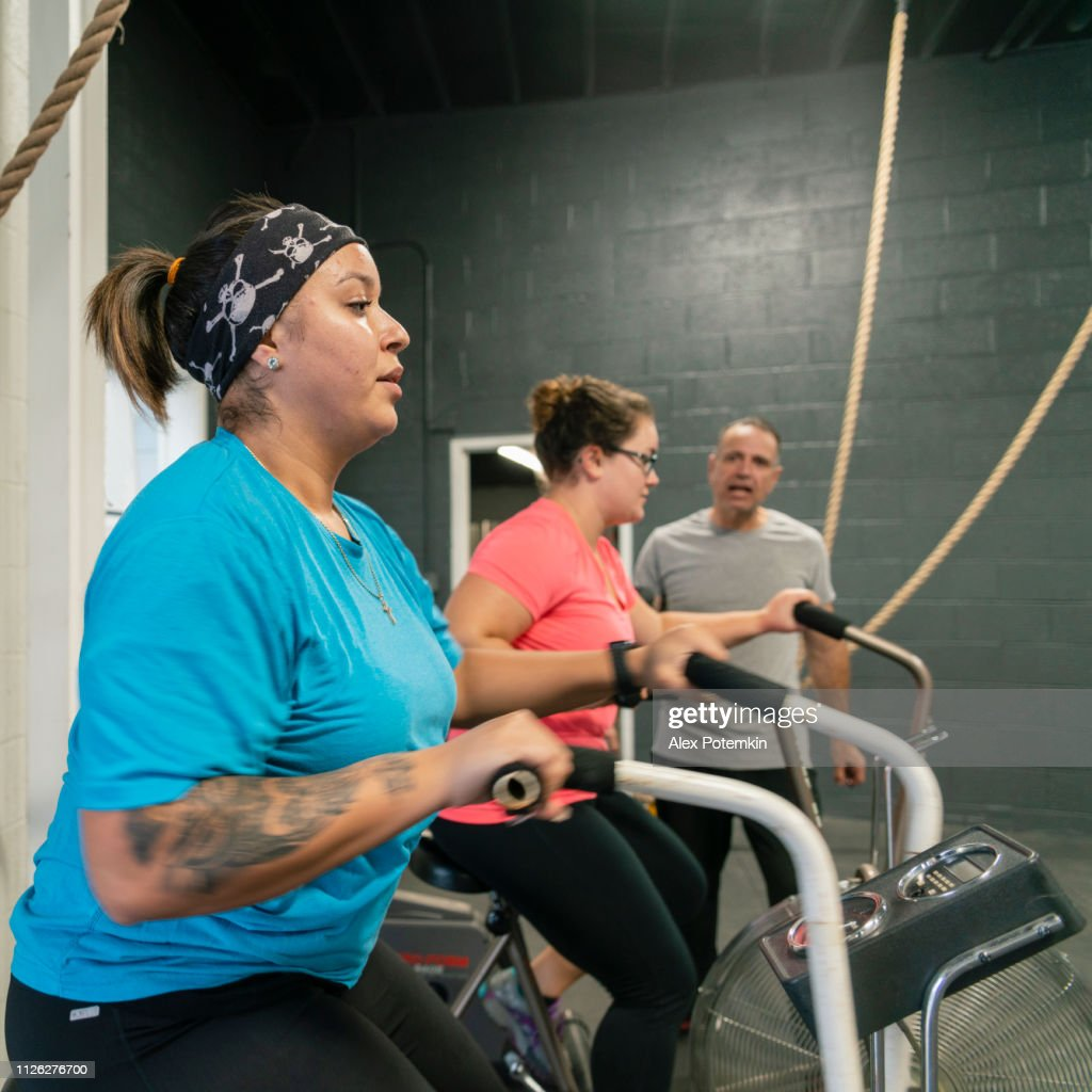 Two attractive body-positive women, Latino and Caucasian, doing a workout on the exercise bike in the gym under the supervision of the coach, the senior 55-years-old Cuban Hispanic man : Stock Photo