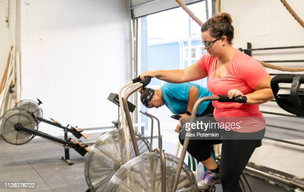 two attractive body-positive women, latino and caucasian, doing a workout on the exercise bike in the gym - alex potemkin or krakozawr latino fitness stock photos and pictures