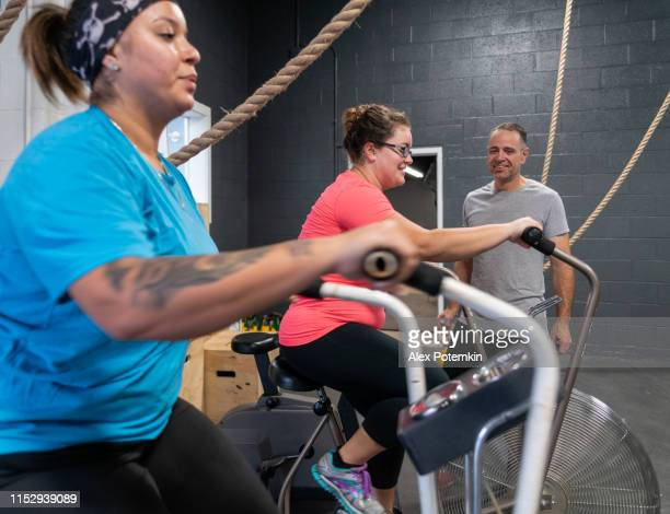 two attractive body-positive women, latino and caucasian, doing a workout on the exercise bike in the gym under the supervision of the coach, the senior 55-years-old cuban hispanic man - 55 59 years stock pictures, royalty-free photos & images