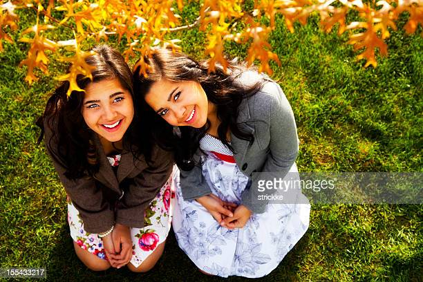 two attractive latina twin females look up under tree branch - identical twin stock pictures, royalty-free photos & images