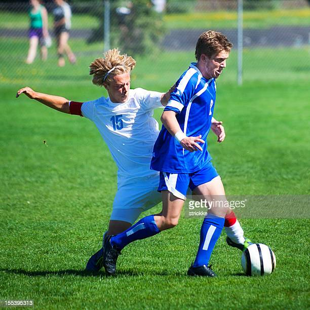 Two Attractive Male Soccer Players in Agressive Tackle from Behind