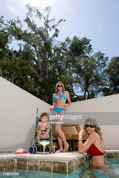 Two attractive women with baby by swimming pool