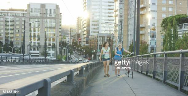 Zwei attraktive junge Frauen Fuß Fahrrad auf Bürgersteig an einem sonnigen Nachmittag
