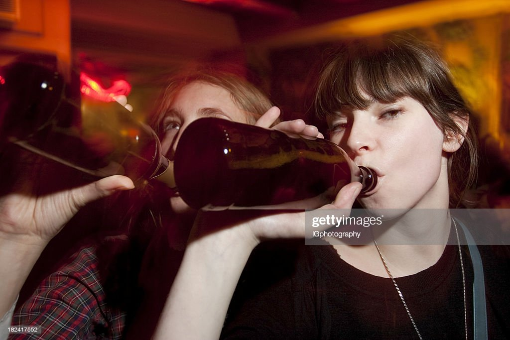 Two Attractive Young Women Drinking Beers at a Bar : Stock Photo