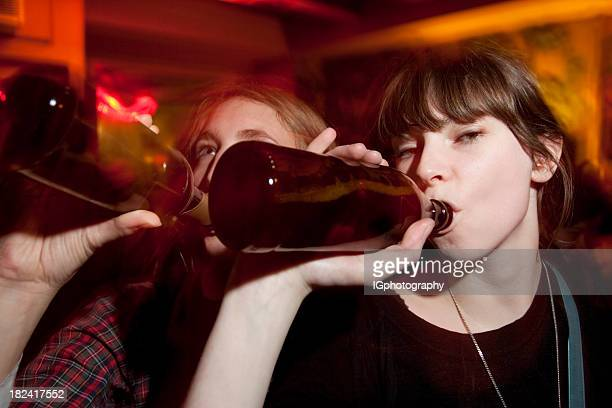 two attractive young women drinking beers at a bar - binge drinking stock photos and pictures