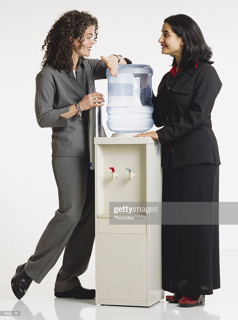 two attractive young women in business attire standing around a water cooler conversing with eachother : Foto de stock