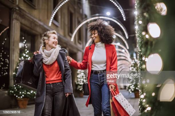 two attractive young women in christmas shopping - feriado imagens e fotografias de stock