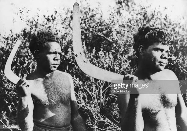 Two Australian Aborigines holding boomerangs circa 1935