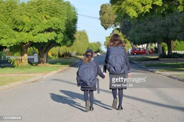 two australian school girl sisters walk to school together - rafael ben ari photos et images de collection