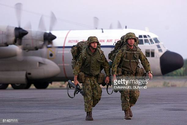 Two Australian soldiers disembark from a military transport plane in Dili East Timor 21 September 1999 at dawn on the second day of the deployment of...