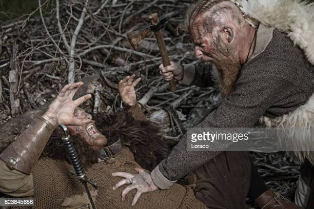 two authentic caucasian bearded viking warriors fighting in outdoor forest setting - barbarian stock photos and pictures
