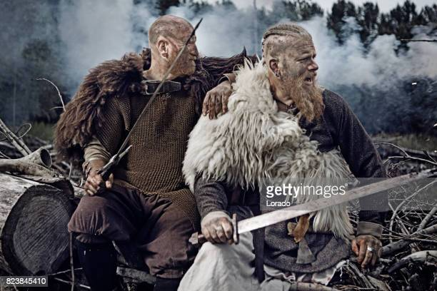 two authentic caucasian bearded viking warriors in outdoor forest setting - barbarian stock photos and pictures