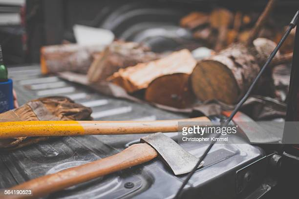Two axes and firewood on a tailgate.