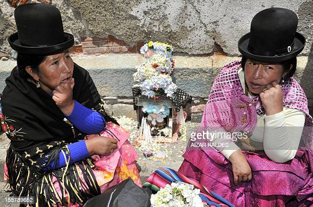 Two Aymara women devotees stay by a 'natita' human skulls from relatives they keep at home for protection at a cemetery in La Paz on November 8 2012...