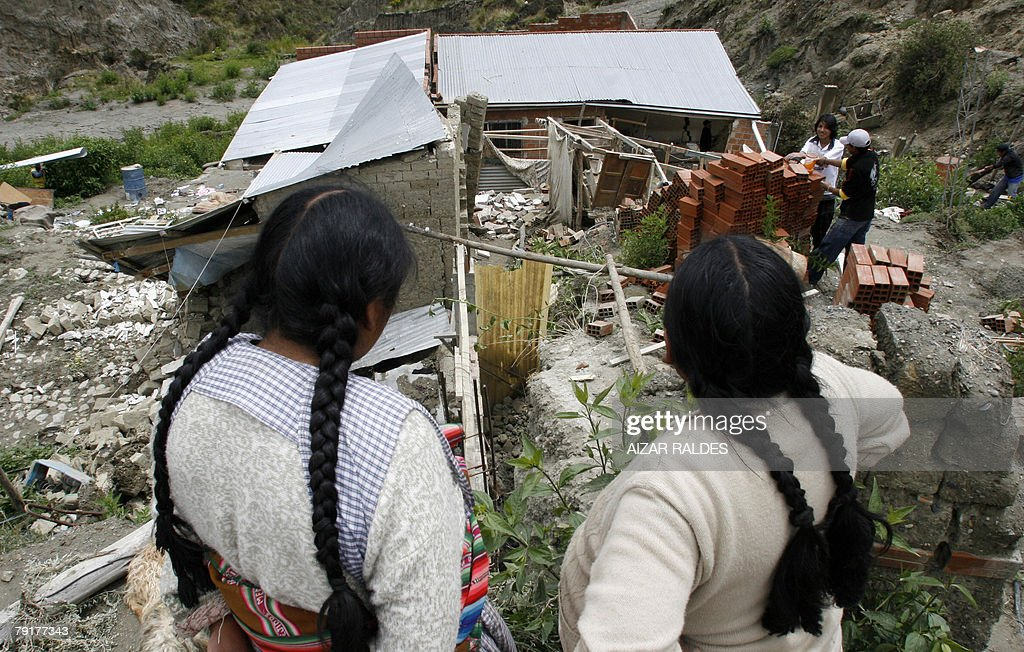 Two aymara women look at the remains of their house 23 January, 2008 in Alpacoma valley in La Paz, after heavy rains caused a landslide that devastated 11 houses. The Bolivian government decreed on Tuesday a national emergency to counteract damages caused by heavy rains and floods battering the country since last November. According to official sources, 22 people died so far and about 20,000 families have been damaged.