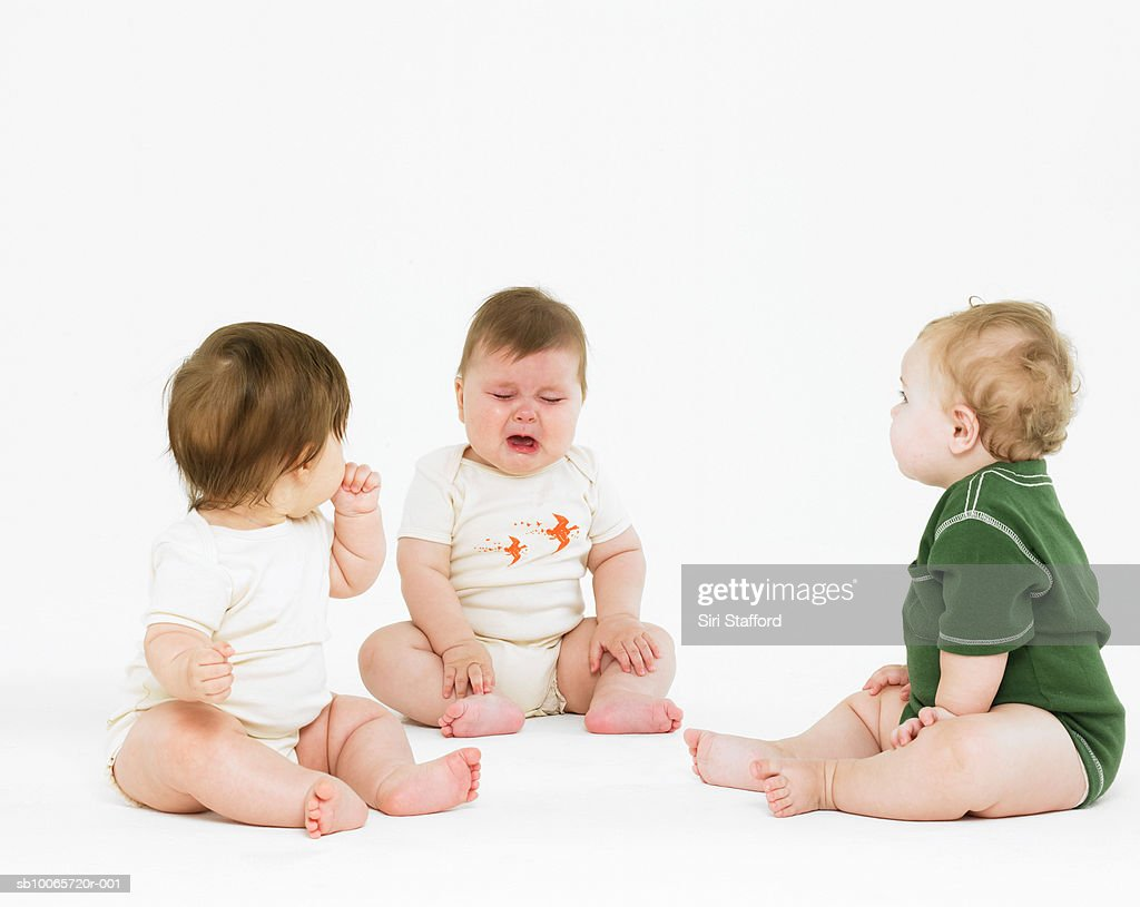 Two babies (6-9 months) looking at third crying : Stock Photo