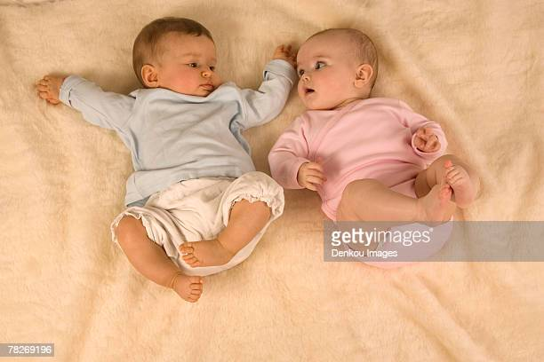 two babies lying down together. - diaper boy stock-fotos und bilder