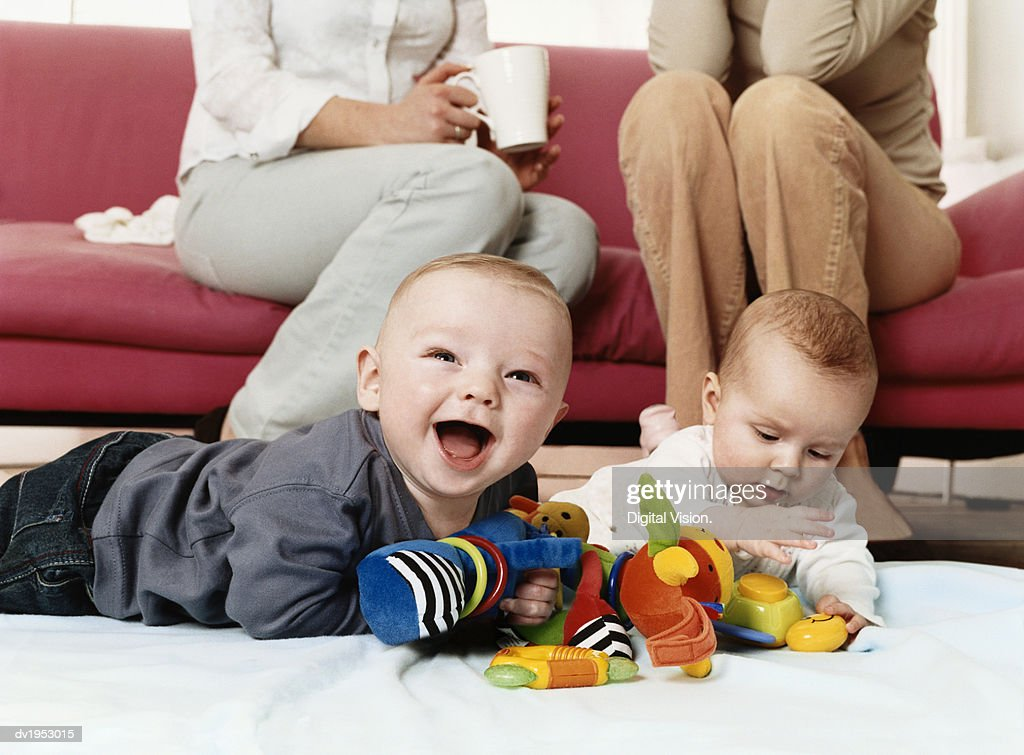 Two Babies Playing with Cuddly Toys on a Living Room Floor : Stock Photo