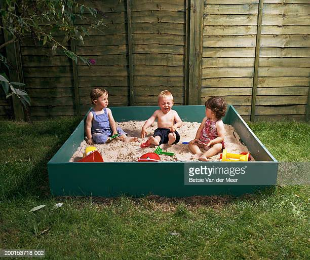 Two baby boys and girl (12-15 month) in sand pit, boy in middle crying