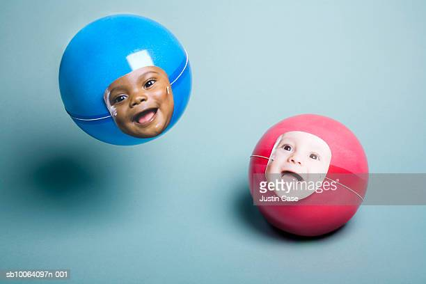 Two baby boy's faces on beach ball, smiling, close-up (digital composite)