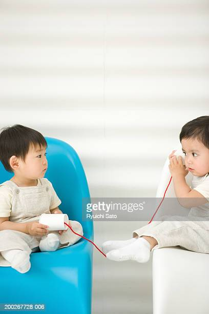 Two baby boys (18-21 months) playing with tin can telephone