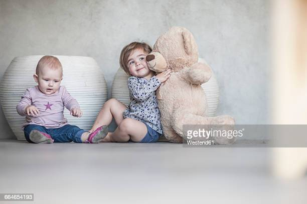 Two baby girls and a teddy bear