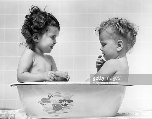 two baby girls in one tub one is holding a sponge the other has hand raised to mouth both are naked inside in the 1960s. - bebe pelado preto e branco imagens e fotografias de stock