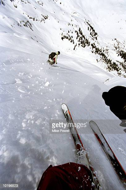 Two back country skiers skiing down snowy moutain