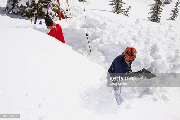 Two backcountry skiers dig an avalanche safety pit near Ymir, British Columbia.