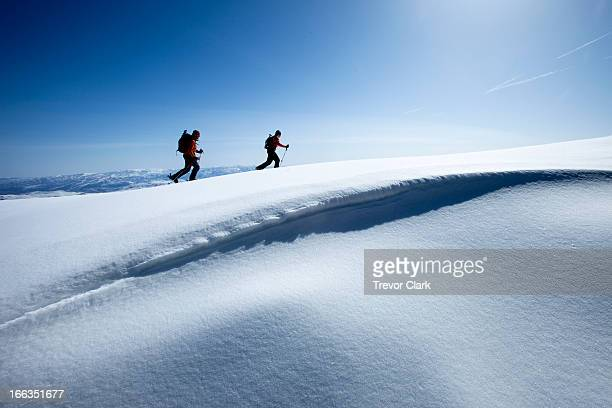 Two backcountry skiers hiking in fresh powder and bluebird skies.