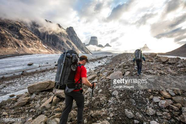 two backpackers hike over glacial moraine to reach mountains ahead. - approaching stock pictures, royalty-free photos & images