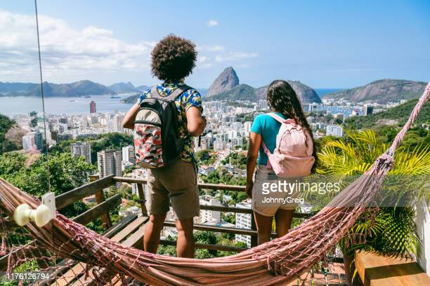 two backpackers looking at view of sugarloaf, rio de janeiro - south america stock pictures, royalty-free photos & images