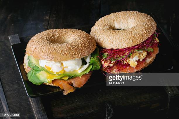Two Bagels with salted salmon spinach beetroot sprouts avocado scrambled and soft boiled egg with liquid yolk on black ceramic square plate over box...