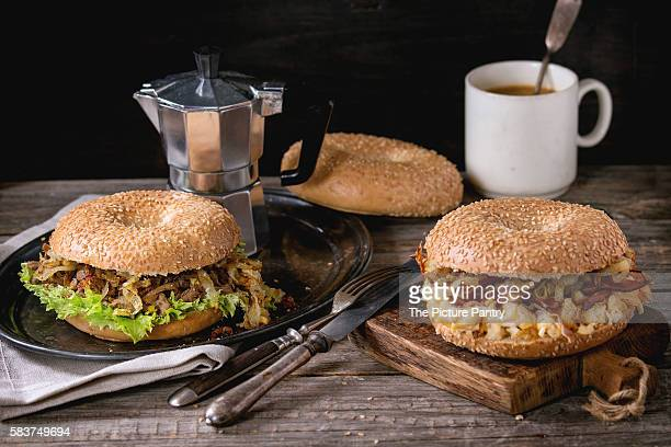 Two Bagels with stew beef, fresh salad, bacon, scrambled eggs and fried onion served on vintage metal tray with cup of coffee and coffee pot