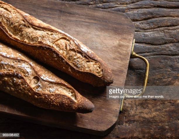 Two baguettes over a wood board on an old piece of wood. Still life.