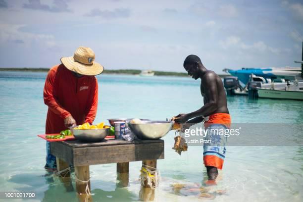 2 つのバハマ ローカル/ネイティブの準備コンクシェル水にスタンドにコンシュ サラダ - ナッソー ストックフォトと画像