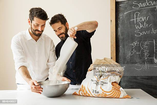 Two bakers standing at a table, preparing bread dough, adding flour from a paper sack into a metal mixing bowl.