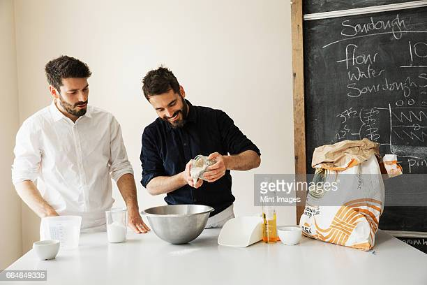 Two bakers standing at a table, preparing bread dough, baking ingredients and a blackboard on the wall.