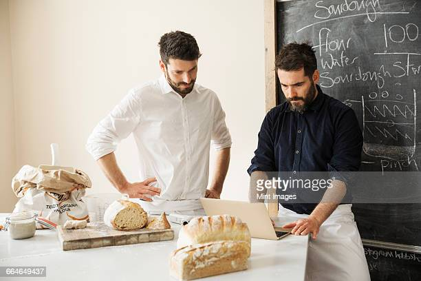 Two bakers standing at a table, using a laptop computer, freshly baked bread, a blackboard on the wall.
