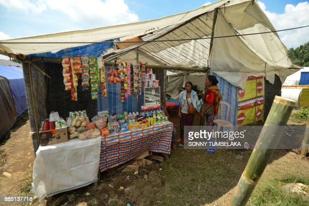 Two Balinese women stand near a small shop at an evacuation center after being evacuated from Mount Agung volcano at Rendang in Karangasem Regency on...