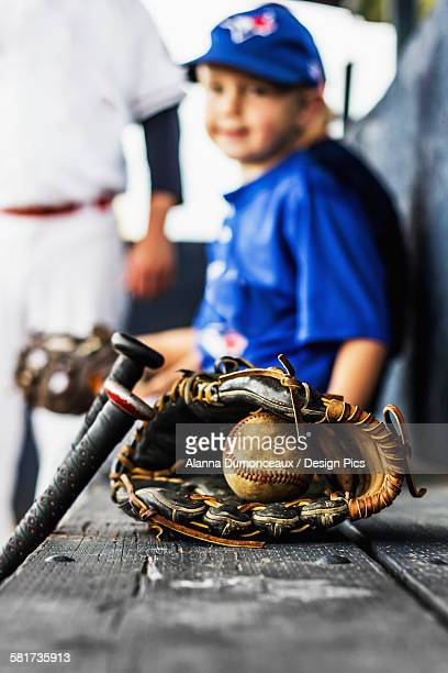 Two ball players in uniform sit in the dugout with their glove and baseball in focus in the foreground