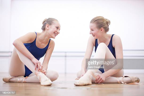 two ballerinas chatting whist fastening ballet slippers - teen girls in tights stock photos and pictures
