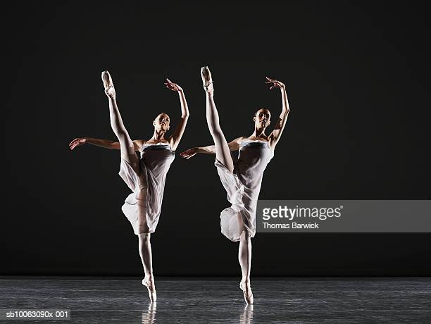 two ballerinas dancing on stage, legs raised - uitvoerende kunst voorstelling stockfoto's en -beelden
