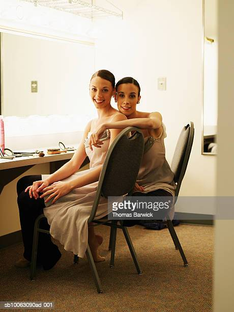 Two ballerinas in costume sitting in dressing room, smiling, portrait
